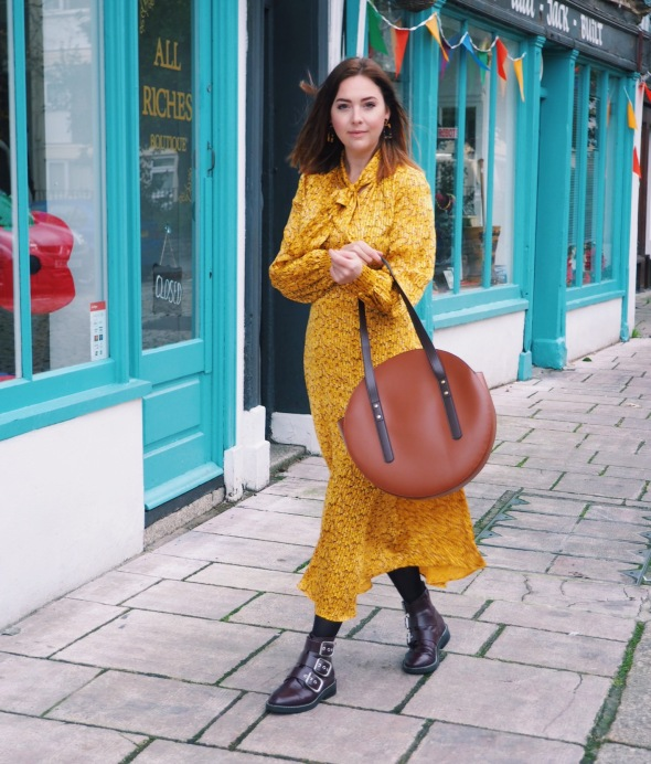 """Fashion Blogger styles the latest Marks and Spencer """"it"""" dress, a flowing yellow midi dress with pussy bow in a subtle leopard print. Worn with chunky buckled boots and a statement shoulder bag."""